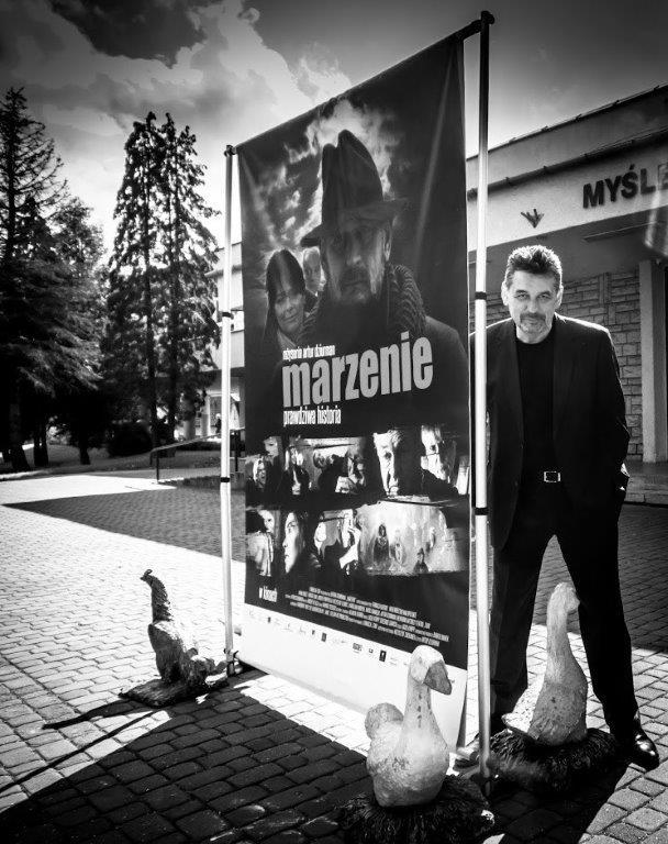 """Artur Dziurman, reżyser filmu stoi przy plakacie filmu """"Marzenie"""" przed Myślenickim Ośrodkiem Kultury i Sportu"""
