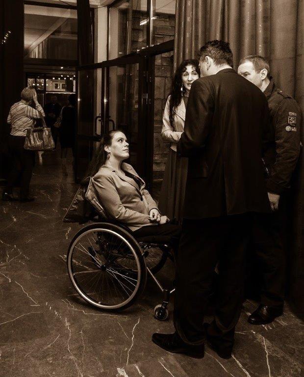 Artur, reżyser rozmawia z widzami po premierze. Dwoje osób w średnim wieku i młoda kobieta na wózku.