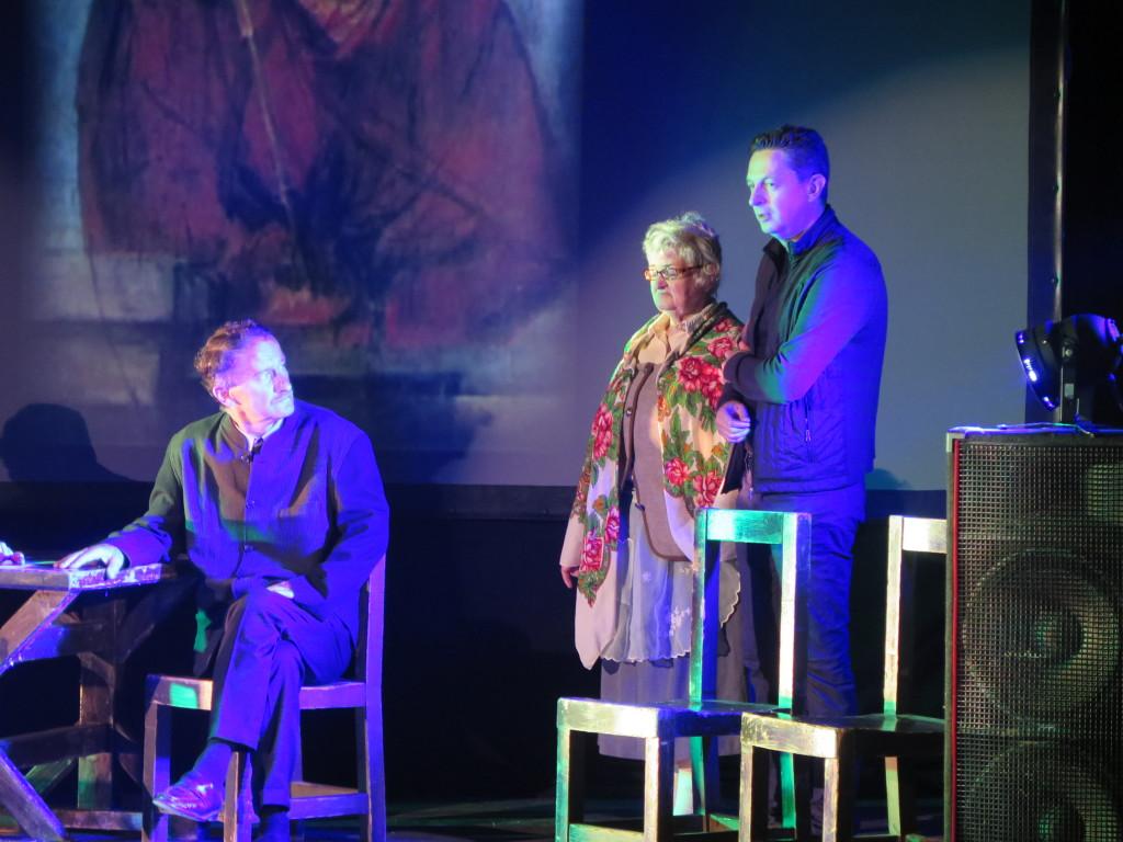 Zdjęcie ze spektaklu Brat naszego Boga w Proszowicach. Aktorzy grają na scenie w tle obraz ecce homo adama chmielowskiego. Mężczyzna przy stole siedzi i patrzy na starszą kobietę, którą trzyma pod ramię mężczyzna w średnim wieku.