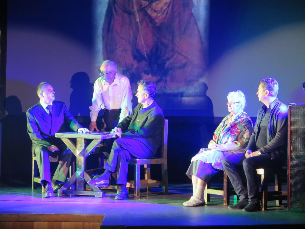 Aktorzy grają na scenie w tle obraz ecce homo adama chmielowskiego. Mężczyzna opiera się o stół i mówi do dwóch innych siedzących przy nim. Obok siedzi mężczyzna i starsza kobieta.