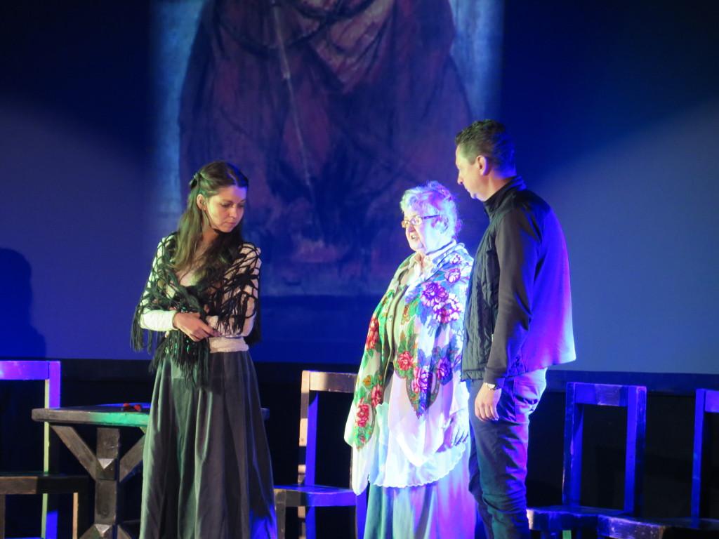Aktorzy grają na scenie w tle obraz ecce homo adama chmielowskiego. Starsza kobieta zwraca się do młodej dziewczyny w długiej sukni, obok odwórcony bokiem mężczyzna.