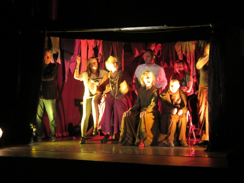 Aktorzy na scenie podczas spektaklu. Scena bezdomnych w ogrzewalni.