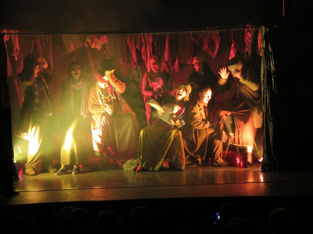 Zdjęcie spektaklu Brat naszego Boga. Scena w ogrzewalni. Aktorzy w łachmanach grają żebraków.