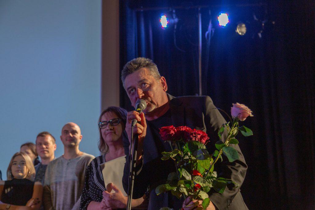 Artur Dziurman na premierze. Trzyma kwiaty w tle aktorzy teatru ITAN.